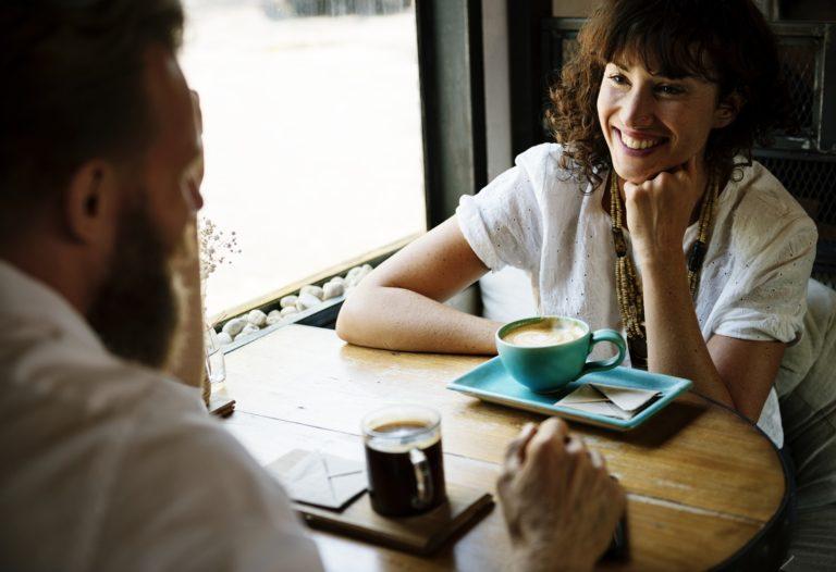 Um homem e uma mulher reunião para café em um pequeno café da moda. Eles têm olhos um para o outro e parecem flertar. Quão fácil pode ser cair em tentação!