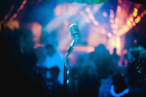 Um microfone aguarda, no centro do palco. Quem virá ao palco? Nós sentimos que eles são cristãos maiores do que nós, porque eles são o centro do palco?