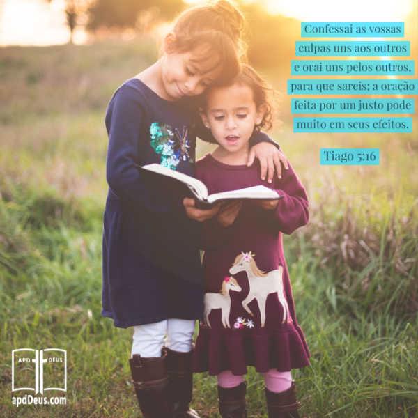 Uma menina está lendo a Bíblia enquanto a mais velha está encorajando a menina mais nova com um braço protetor em volta do ombro. Tiago 5:16