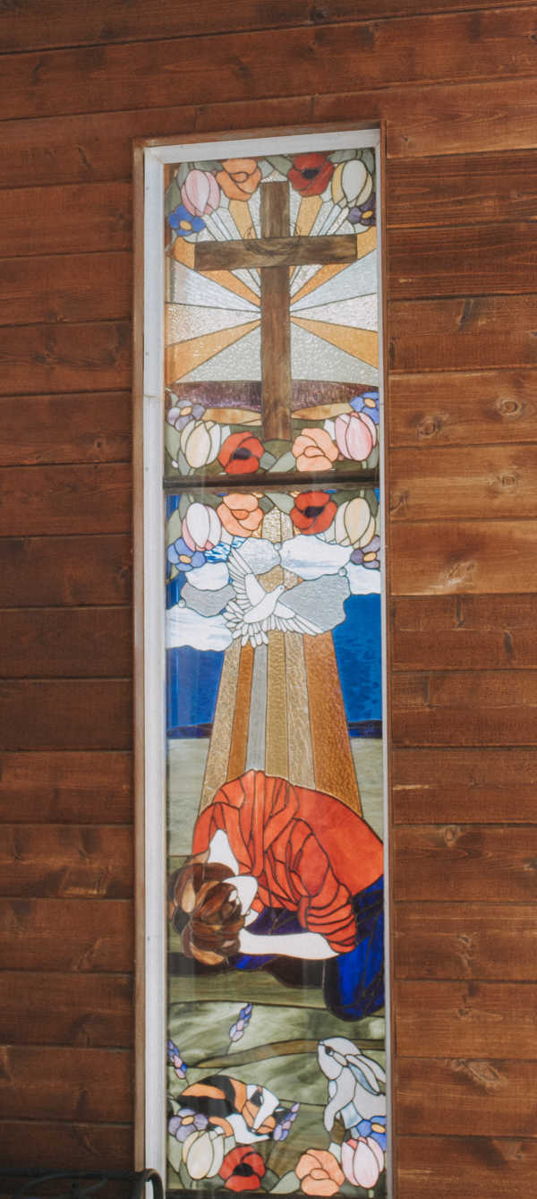 Um vitral representando alguém que está orando ao pé da cruz.