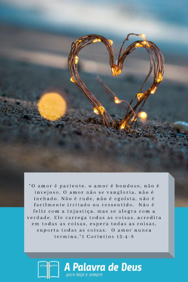 Um coração entrelaçado com pequenas luzes se projeta da areia. As palavras de 1 Coríntios 13:4-8 são escrita