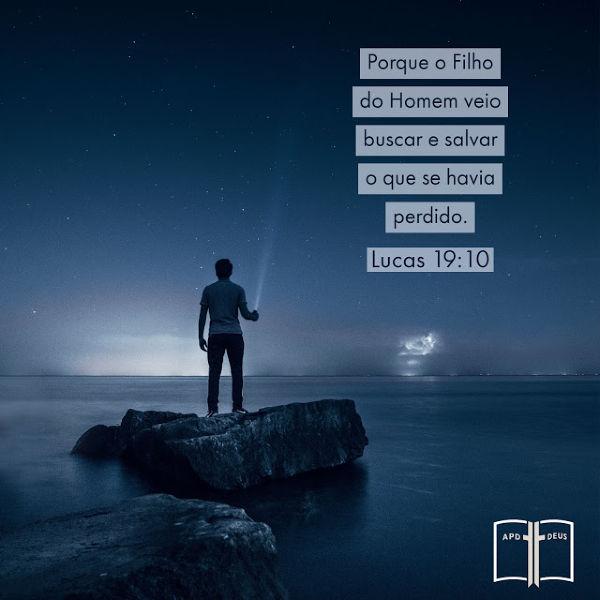 Um homem está à beira de um lago apontando uma lanterna para o céu estrelado da noite. Lucas 19:10
