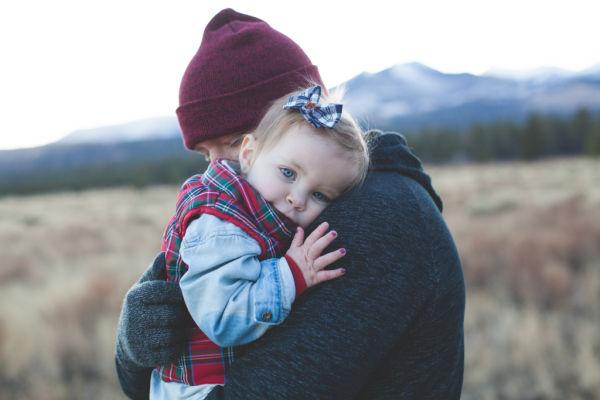 Uma menina pequena de olhos azuis está aninhada nos braços de seu pai, como estamos com o Pai Deus.
