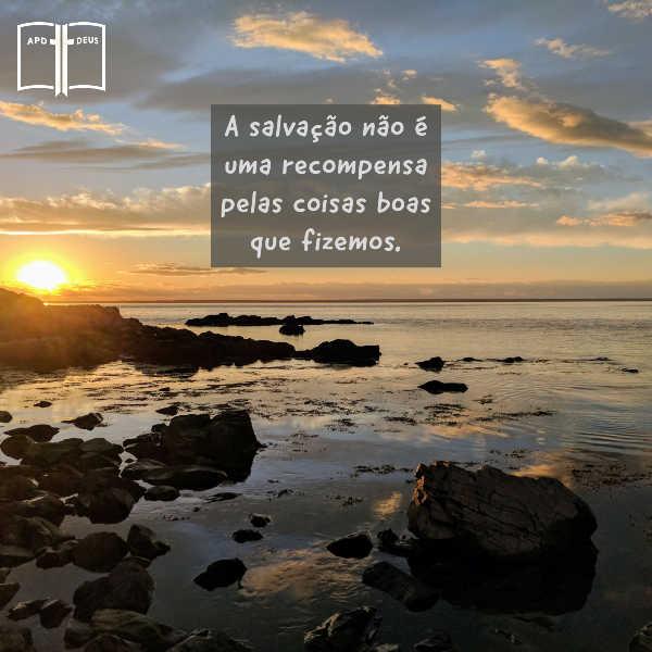 O sol brilha sobre a costa rochosa de um lago com as palavras: A salvação não é uma recompensa pelas coisas boas que fizemos.