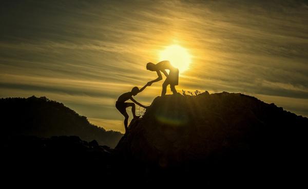 Um jovem levanta outro jovem até a última parte de uma montanha, enquanto o sol se põe no fundo.