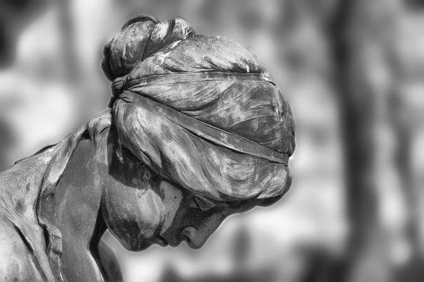 Uma estátua com a cabeça baixa.